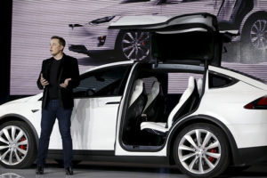 Tesla CEO Elon Musk introduces the falcon wing door on the Model X electric sports-utility vehicles during a presentation in Fremont, Calif.