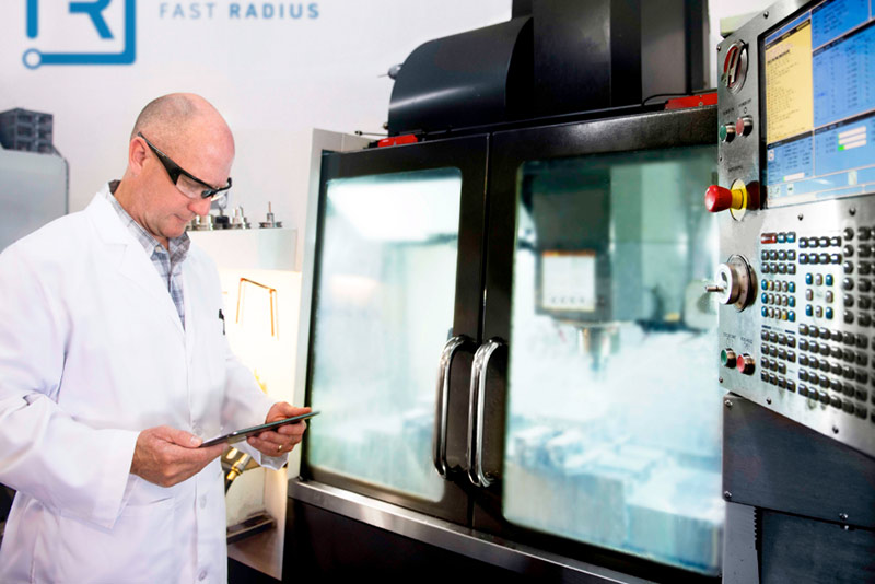 Fast Radius employee monitors 3D printing machine for UPS