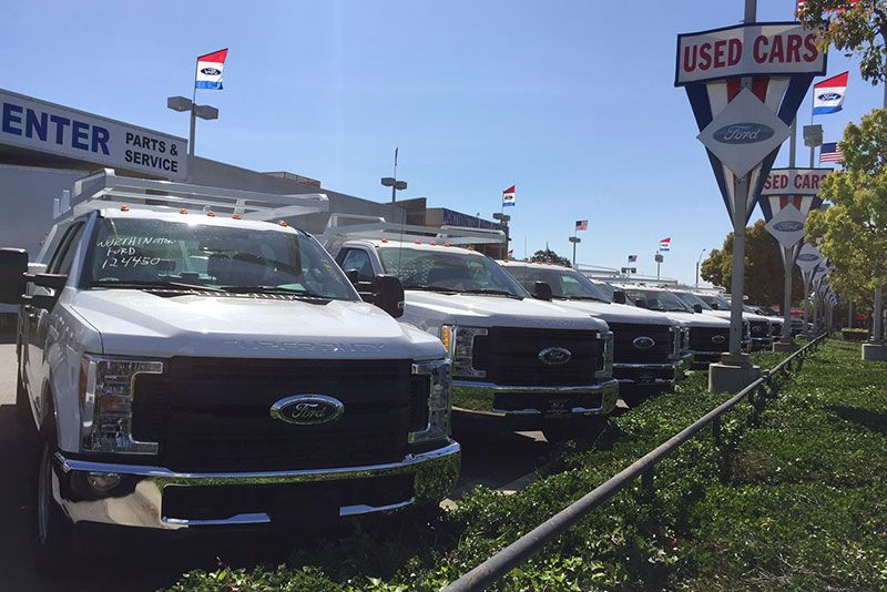 Used trucks on the dealership lot grilles