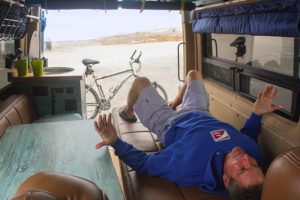 Eric Lizerbram lying in his custom sprinter van
