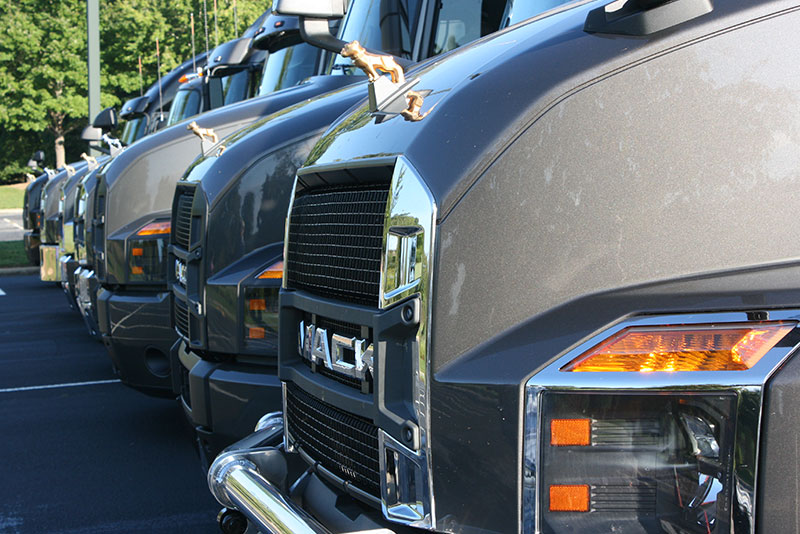 Trucks lined up for Day 2. Note contrast between chrome finish on near truck and available black on next vehicle. Gold Bulldog indicates all-Mack powertrain.