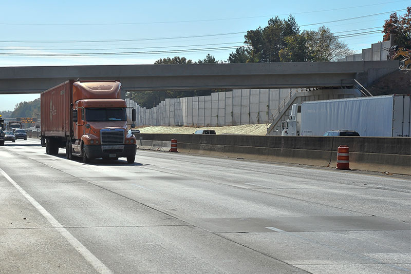 Trucks on I-285 East drive past contruction for express lanes